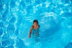 Menino que relaxa na piscina durante férias Imagem de Stock Royalty Free