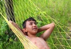 Menino que relaxa no hammock Fotos de Stock Royalty Free