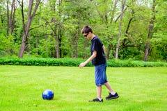 Menino que retrocede a esfera de futebol Fotos de Stock