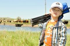 Menino que reune vacas em um prado Fotografia de Stock Royalty Free