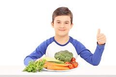 Menino que senta-se atrás de uma placa completamente de legumes frescos Fotos de Stock