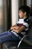 Menino que senta-se com passaporte e passagem de embarque no aeroporto Fotos de Stock