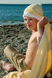 Menino que senta-se com uma toalha na praia Imagens de Stock Royalty Free