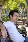 Menino que senta-se em um parque Fotos de Stock