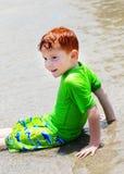 Menino que senta-se na água pouco profunda Fotos de Stock Royalty Free