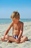 Menino que senta-se na areia pelo mar Imagem de Stock