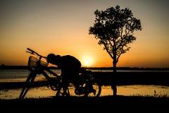 Menino que senta-se na bicicleta no rio da noite, fundo do por do sol Fotos de Stock Royalty Free