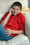 Menino que senta-se na cadeira que fala no telefone de pilha foto de stock