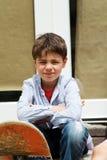 Menino que senta-se na frente da porta Fotografia de Stock