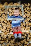 Menino que senta-se na madeira com um quadro vazio da imagem imagens de stock royalty free