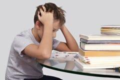 Menino que senta-se na tabela de vidro cercada pelos livros que guardam a cabeça Foto de Stock