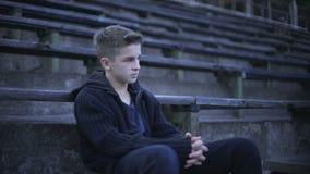 Menino que senta-se na tribuna, na devastação e na pobreza do estádio ao redor, cidade após a guerra video estoque