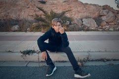 Menino que senta-se no asfalto fotografia de stock royalty free