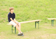 Menino que senta-se no banco Imagem de Stock Royalty Free