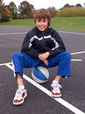 Menino que senta-se no basquetebol Fotos de Stock Royalty Free
