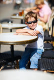 Menino que senta-se no café ao ar livre Imagens de Stock Royalty Free