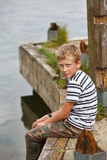 Menino que senta-se no cais de madeira velho Fotos de Stock Royalty Free