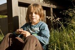 Menino que senta-se no jardim Fotografia de Stock