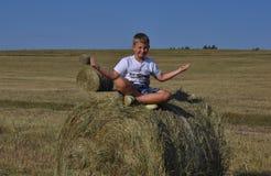 Menino que senta-se no monte de feno no prado Imagem de Stock