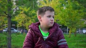 Menino que senta-se no parque em um banco O ` s perdeu, esperando seus pais video estoque