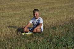 Menino que senta-se no prado Imagem de Stock