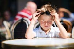 Menino que senta-se no restaurante ao ar livre Imagem de Stock Royalty Free