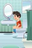 Menino que senta-se no toalete no banheiro Imagem de Stock