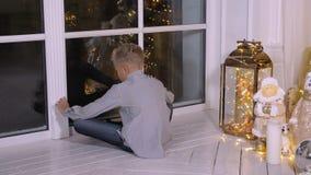 Menino que senta-se perto da janela na Noite de Natal e de Santa Claus de espera na sala de visitas filme