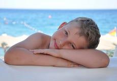 Menino que senta-se perto do mar Imagens de Stock