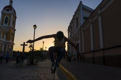Menino que skateboarding em uma rua da cidade colonial de Granada em Nicarágua no por do sol Imagem de Stock Royalty Free