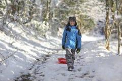 Menino que sledding para fora na neve foto de stock royalty free