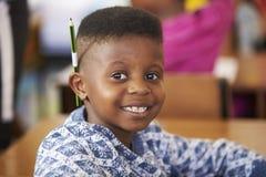 Menino que sorri à câmera em uma lição da escola primária fotos de stock