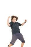 Menino que sorri com expressão da cara e que salta no t-shi escuro preto Foto de Stock