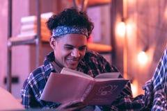 Menino que sorri surpreendentemente candidly à história romântica ele leitura em seu livro imagens de stock royalty free