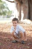 Menino que squatting no parque fotografia de stock