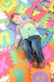Menino que tem o divertimento encontrar-se em letras do alfabeto dos miúdos Imagem de Stock Royalty Free