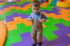 Menino que tem o divertimento no parque de diversões das crianças e no centro interno do jogo Criança que joga com os brinquedos  Fotografia de Stock