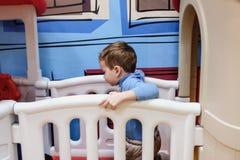 Menino que tem o divertimento no parque de diversões das crianças e no centro interno do jogo Criança que joga com os brinquedos  Fotos de Stock Royalty Free