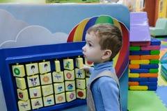 Menino que tem o divertimento no parque de diversões das crianças e no centro interno do jogo Criança que joga com os brinquedos  Fotografia de Stock Royalty Free