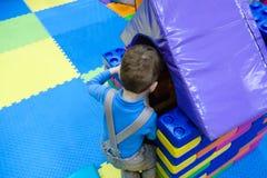 Menino que tem o divertimento no parque de diversões das crianças e no centro interno do jogo Criança que joga com os brinquedos  Imagens de Stock Royalty Free