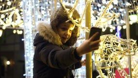 Menino que toma o selfie no quadrado perto da árvore de Natal vídeos de arquivo