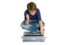 Menino que trabalha em um portátil Fotografia de Stock Royalty Free