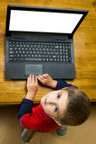 Menino que trabalha em um portátil Foto de Stock Royalty Free