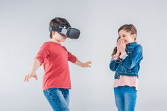 Menino que usa auriculares da realidade virtual quando menina que olha nele fotos de stock