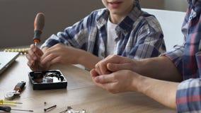 Menino que usa a chave de fenda para reparar o disco rígido, ensino do pai, dando algum conselho video estoque