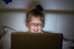 Menino que usa o portátil na cama na noite Foto de Stock