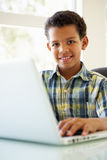 Menino que usa o portátil em casa Imagens de Stock Royalty Free