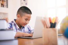 Menino que usa seu portátil à aprendizagem em linha fotografia de stock