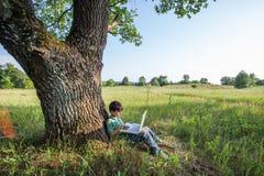 Menino que usa seu portátil exterior no parque na grama Fotos de Stock Royalty Free