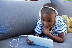 Menino que usa a tabuleta digital ao escutar fones de ouvido no sofá em casa fotografia de stock royalty free